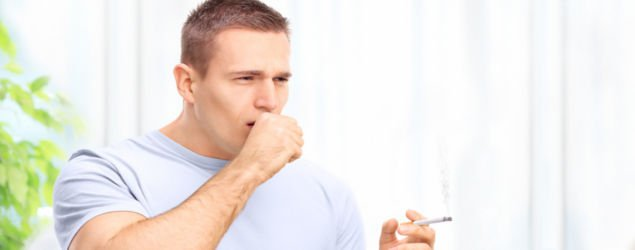 Young man smoking a cigarette and coughing