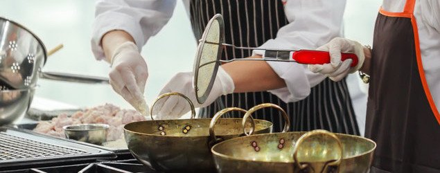 two chefs cooking food in wok
