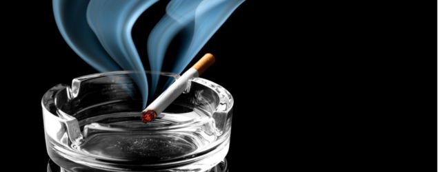 Closeup of cigarette on ashtray with a wisp of smoke