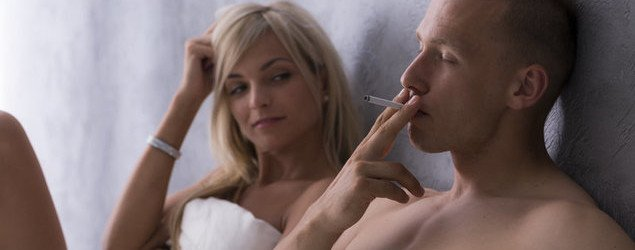 couple in bed man smoking a cigarette