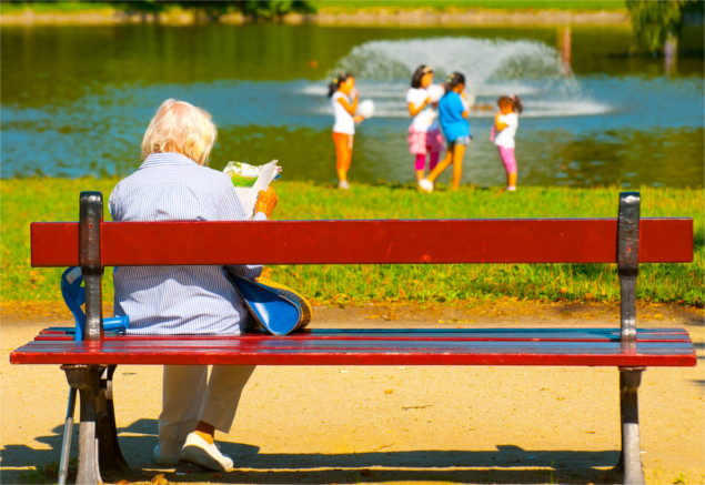 Old woman sitting on bench in park with kids on pond in the background