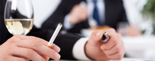 Close-up of a businessman drinking wine and smoking cigarettes