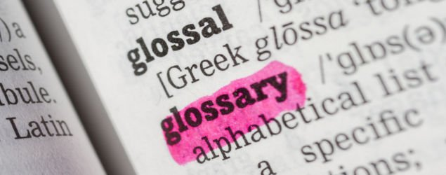 Glossary highlighted in dictionary with pen closeup