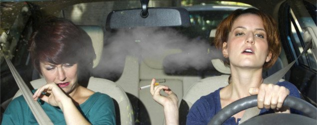 young female smoking while driving inside the car