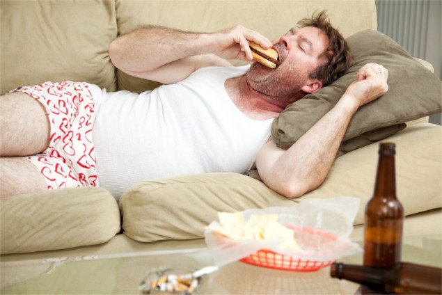 Unemployed middle aged man at home on the couch in his underwear, eating a hamburger