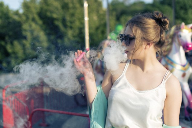 young woman vapes a pink vaping device