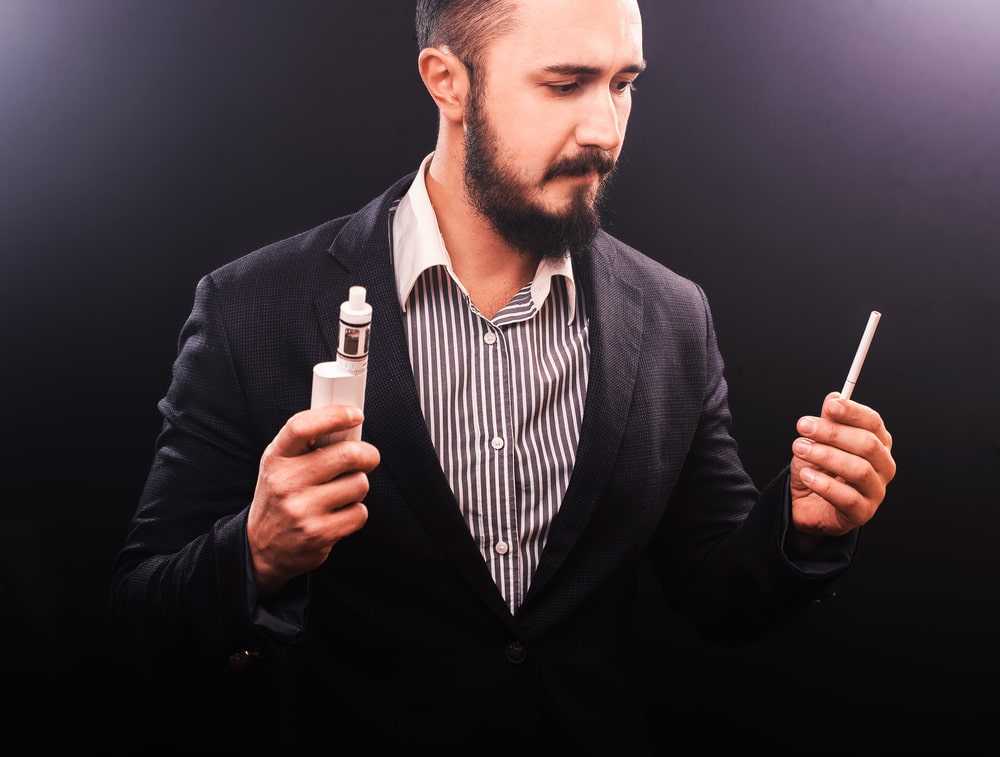 man makes a choice between cigarette and vape