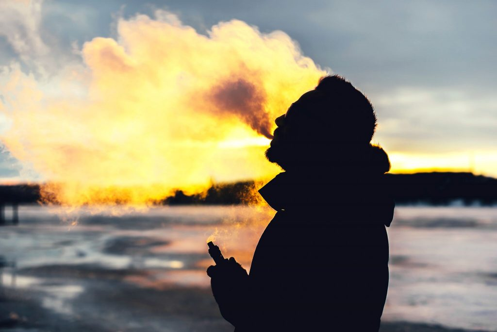 man smokes electronic cigarette outdoor on the fire background