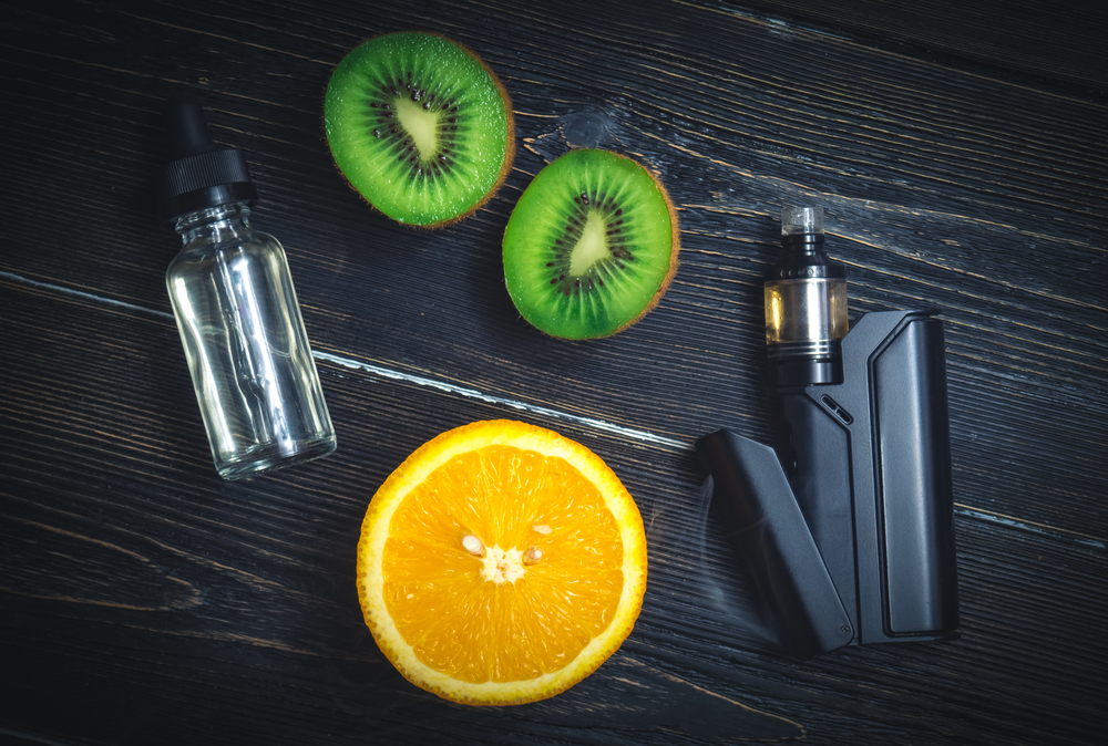 vape device, e-juice and fruits on the table
