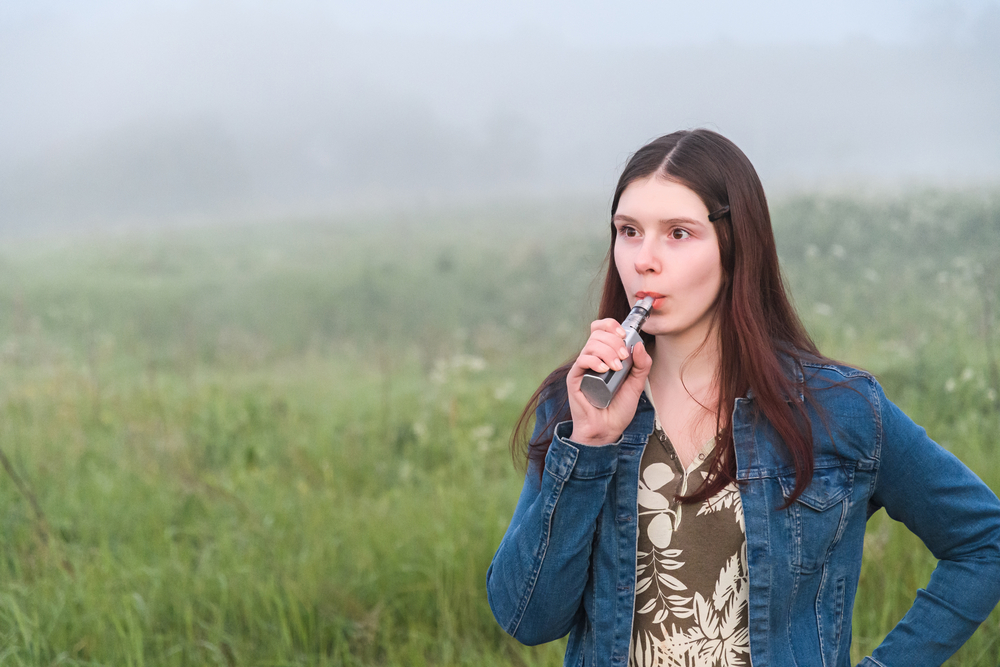 girl vaping with a landscape in the background