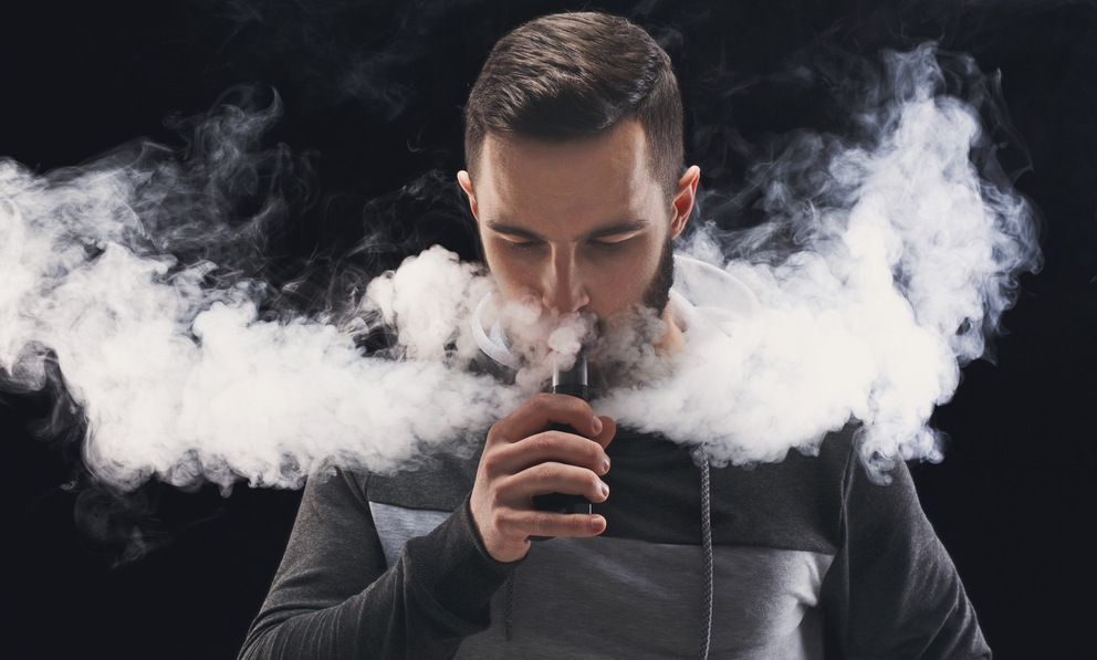 Man vaping on a dark background