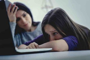 Scared mother arguing daughter over online activity