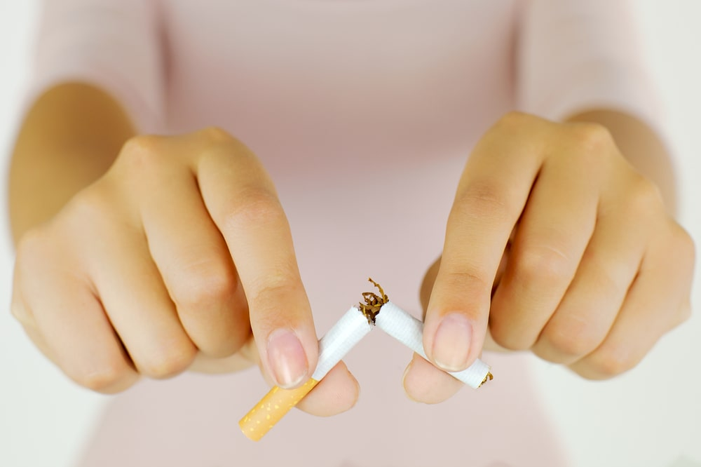 Hands of woman destroying cigarette