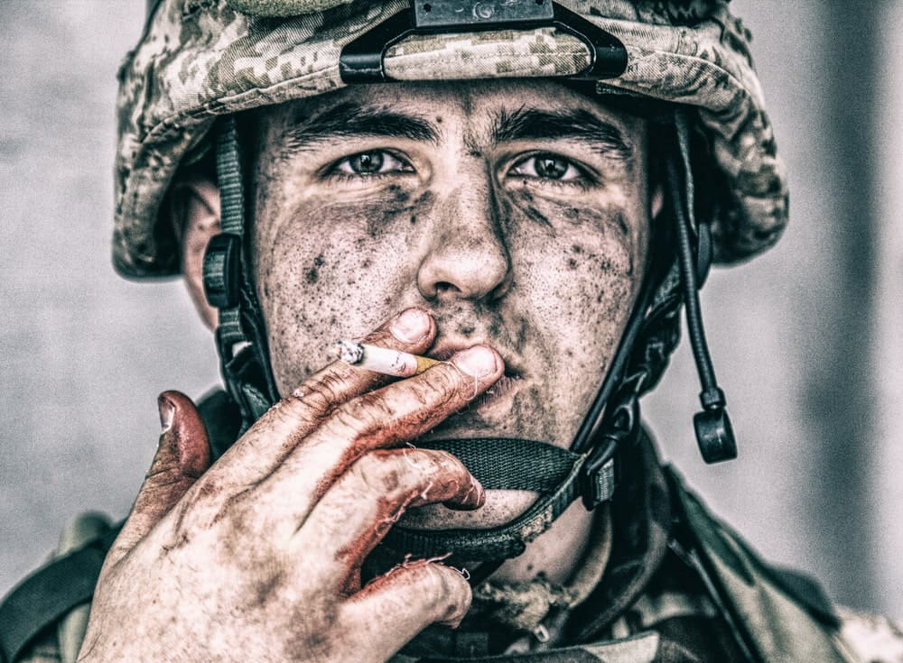 U.S. marine with dirty face holding cigarette