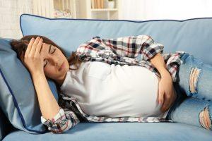 sick pregnat on a sofa