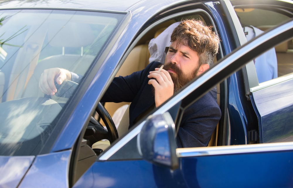 Man bearded smoking cigarette in car