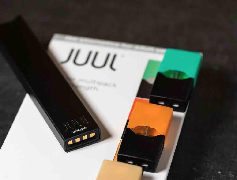 Juul e-cigarette or nicotine vapor dispenser box on slate