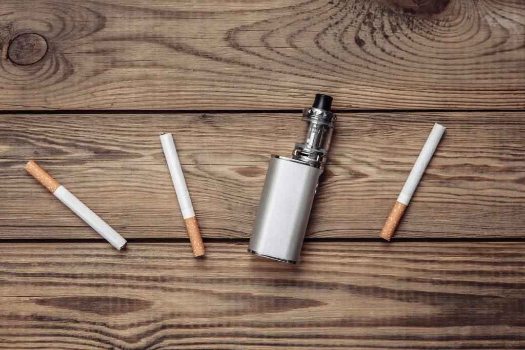 Vaping device and cigarettes on wooden table